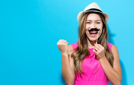 Joven mujer sosteniendo partido de papel palos sobre un fondo de color sólido Foto de archivo - 81929003