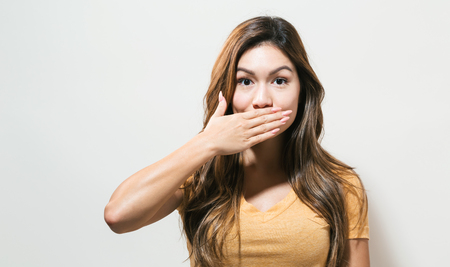 Young woman covering her mouth on a off white background Imagens