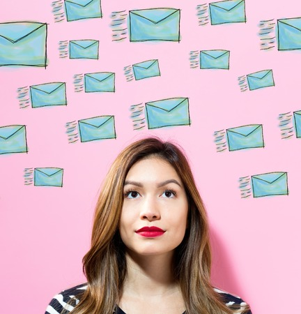 Emails with young woman on a pink background Stock Photo