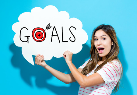 Goals text with young woman holding a speech bubble on a blue background