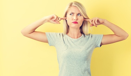 Young woman blocking her ears on a yellow background Stock Photo
