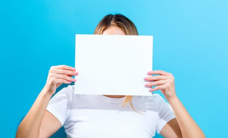 one sheet: Woman holding a blank sheet of paper in front of her face