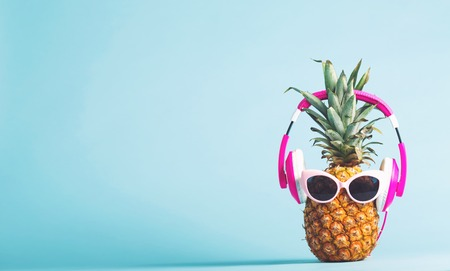 Pineapple with headphones and glasses on a bright background Imagens