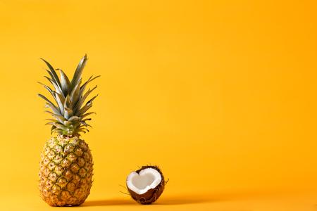 Gehele ananas en verse kokosnoot op een heldere gele achtergrond Stockfoto