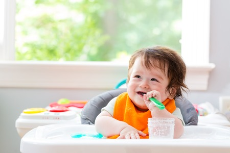 Happy little baby boy eating food with a spoon
