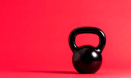 Black cast iron kettlebell on a red background
