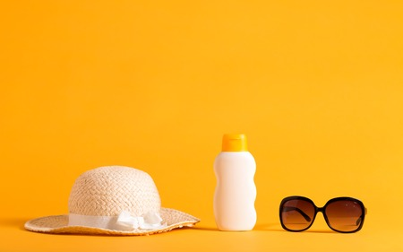 Summer sun protection objects theme on a yellow background Foto de archivo