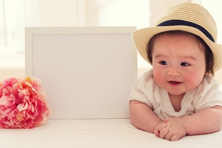 Happy baby boy with a white photo frame and a pink flower Standard-Bild