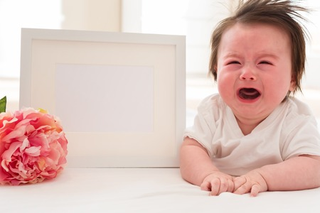 Crying baby boy with a white photo frame and a pink flower