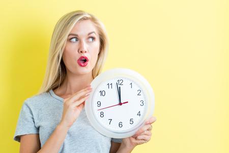 Young woman holding a clock showing nearly 12 Фото со стока
