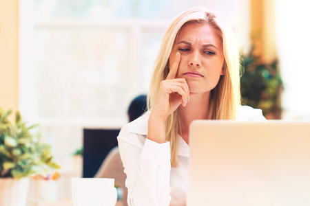 Unhappy young woman sitting at her desk in front of the computer