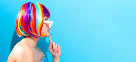 Beautiful woman in a colorful wig on a blue background