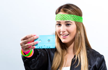 Woman in 1980s fashion holding a cassette tape on a white background