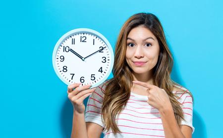 青色の背景に時計を保持している若い女性 写真素材