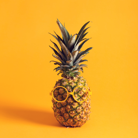 Whole pineapple with glasses on a bright yellow background