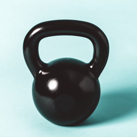 Black cast iron kettlebell on a blue background