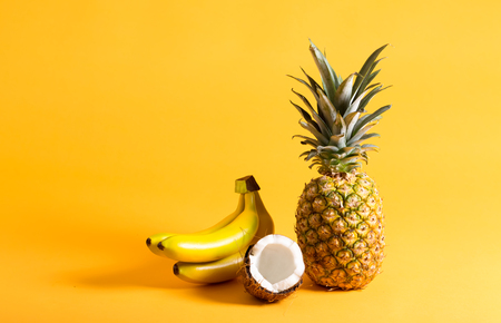 Pineapple, bananas and fresh coconut on a bright yellow background