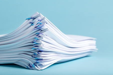 Pile of papers organized with paper clips on a blue background Banco de Imagens