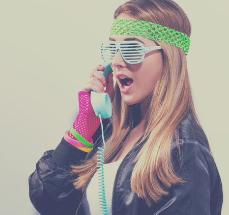 Woman in 1980s fashion with old fashioned phone on a white background Standard-Bild