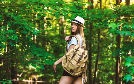 Jonge vrouw in het bos met een rugzak en hoed Stockfoto
