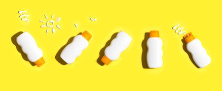 밝은 노란색 배경에 배치 된 자외선 차단제 병