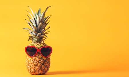 Whole pineapple with sunglasses on a bright yellow background Imagens