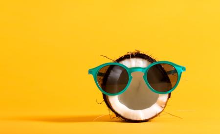 明るい黄色の背景にサングラスを着て新鮮なココナッツ