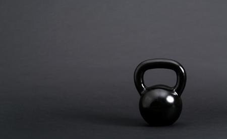 Black cast iron kettlebell on a black background