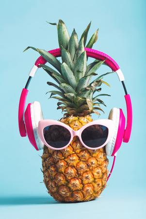 Ananas met hoofdtelefoons en glazen op een heldere achtergrond