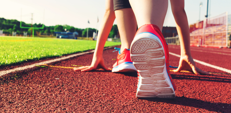 Female athlete on the starting line of a stadium track preparing for a run Stock Photo