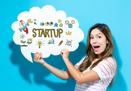 Start Up text with young woman holding a speech bubble on a blue background Stock Photo