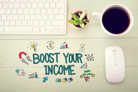 Boost Your Income concept with workstation on a light green wooden desk Stock Photo