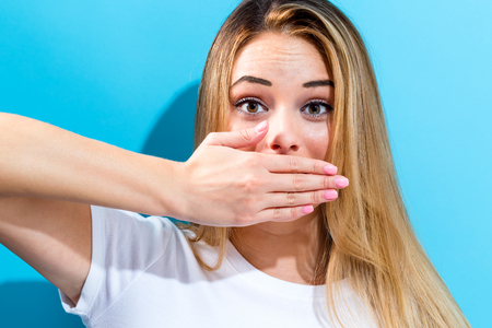 Young woman covering her mouth on a blue background Stok Fotoğraf
