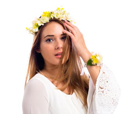 Mooie jonge vrouw met een bloemkrans en een witte jurk geïsoleerd op een witte achtergrond