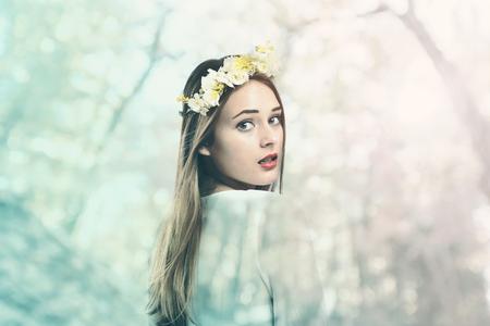 花輪および白いドレスの美しい若い女性