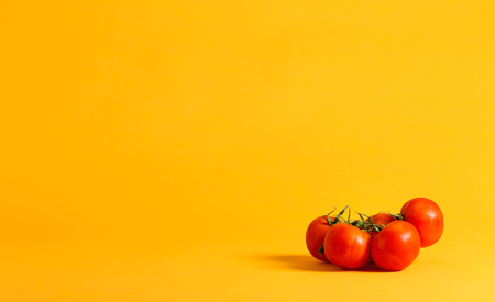 Group of whole red tomatos on a yellow background
