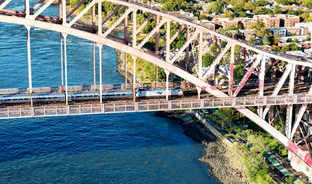 NEW YORK - JULY 02 2016: Aerial view of and Amtrak train crossing the Hell Gate Bridge in New York City