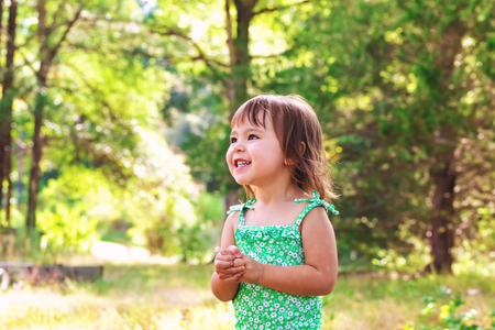 Happy toddler girl wearing bathing suit playing outside Stock Photo