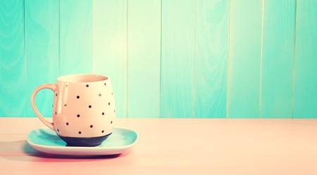 밝은 파스텔 핑크색과 파란색 배경에 커피 잔