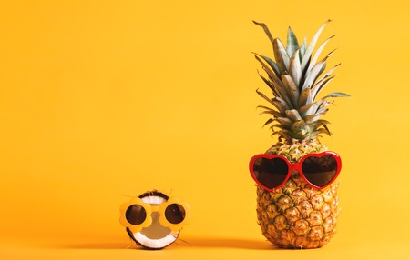 Pineapple and coconut wearing sunglasses on a bright yellow background