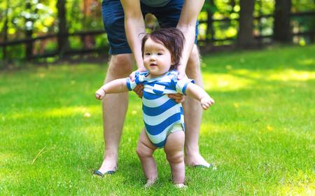 Neonato che impara a camminare fuori con l'aiuto dei suoi genitori Archivio Fotografico - 82805060