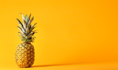 Whole pineapple on a bright yellow background