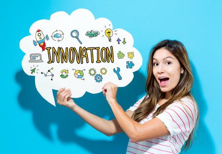 青い背景の吹き出しを保持している若い女性とイノベーション本文 写真素材
