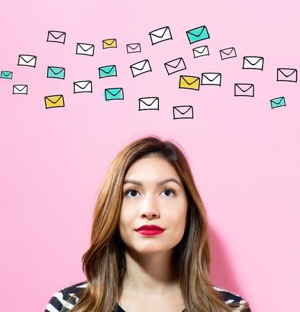 ピンクの背景の若い女性とメール