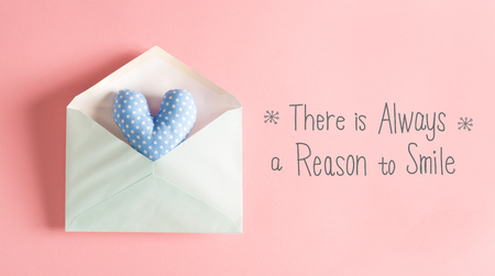 There Is Always A Reason To Smile message with a blue heart cushion in an envelope Stock Photo