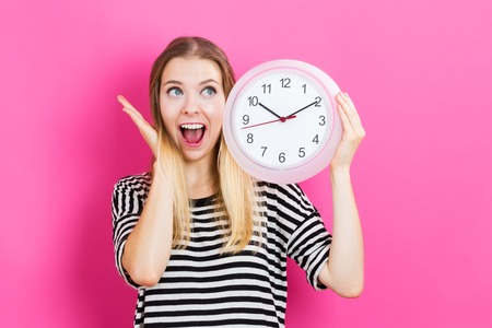 Young woman holding a clock on a pink background