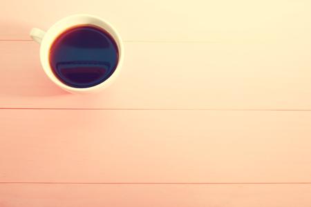 밝은 파스텔 핑크 배경에 커피 잔