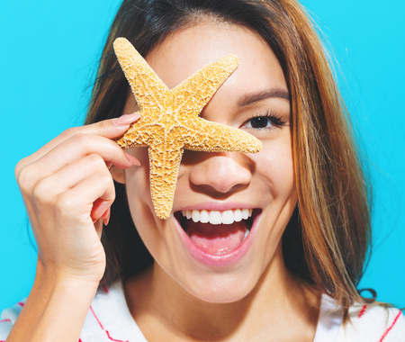 Happy woman summer theme with a starfish held up to her face