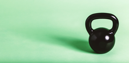 Black cast iron kettlebell on a green background Stock Photo