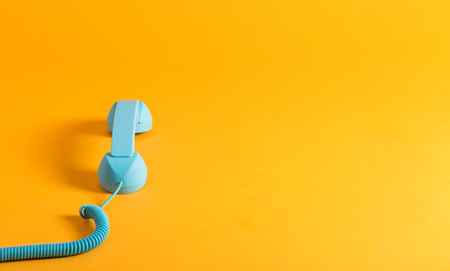 handset: Vintage style blue telephone handset on a yellow background